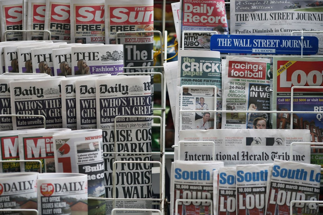 Newspapers are displayed on a stand outside a newsagent -1464267