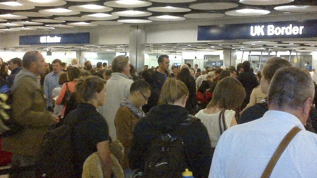 Travellers queue to be processed by UK Border Agency immigration control officers at Heathrow airport's Terminal 5 in London