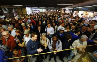Hundreds of flight passengers wait past closed security gates during a strike in Frankfurt airport