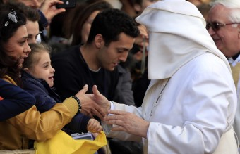 A gust of wind blows Pope Francis's mantle as he greets the faithful at the S. Maria della Provvidenza church in Rome