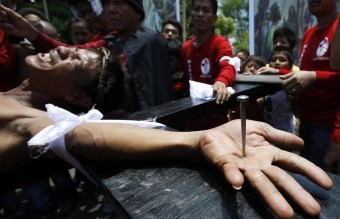 Penitent Danilo Ramos grimaces in pain as he is nailed to a wooden cross during the reenactment of the death of Jesus Christ on Good Friday in San Fernando