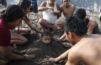 A family helps bury a boy in sand at a beach to celebrate Easter Sunday in Cavite