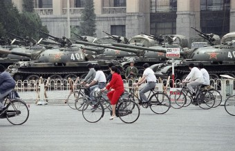 June 13, 1989 - A Wall of Tanks and APCs Greet Bicycle Commuters (AFP)