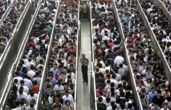 A security officer stands guard as passengers line up and wait for a security check during morning rush hour at Tiantongyuan North Station in Beijing