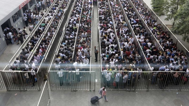 Passengers line up and wait for a security check during morning rush hour at Tiantongyuan North Station in Beijing