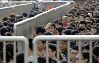 A man looks up as he lines up with other passengers and waits for a security check during morning rush hour at Tiantongyuan North Station in Beijing