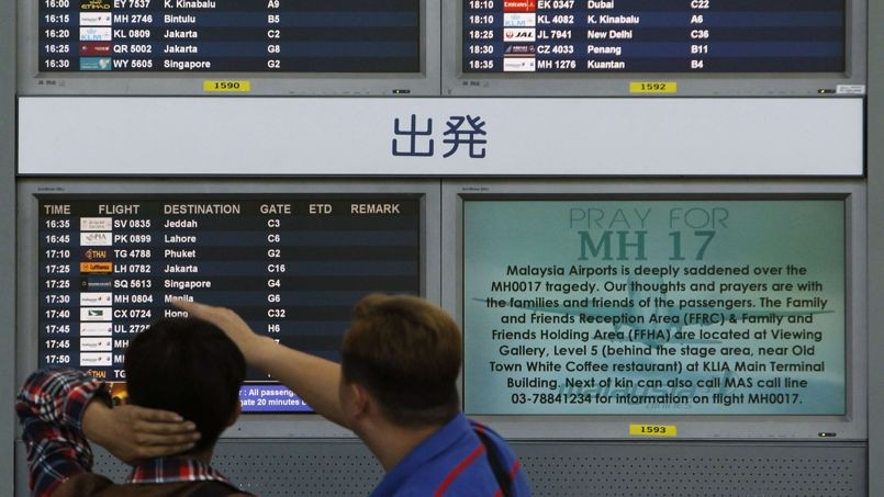 "Bystanders look at board displaying flight information and ""Pray for MH17"" message at Kuala Lumpur International Airport in Sepang"
