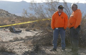 Two volunteer search and rescue sheriff's deputies stand near a piece of debris is seen near the crash site of Virgin Galactic's SpaceShipTwo near Cantil