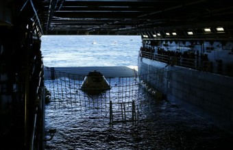 A test version of NASA's Orion capsule floats in the rear of the USS Anchorage during a recovery drill off the coast of California