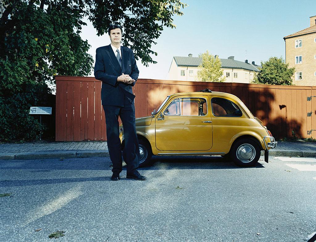 висок мъж  с малка кола