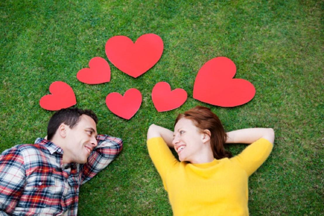флирт, мъж и жена лежат на поляна, сърца