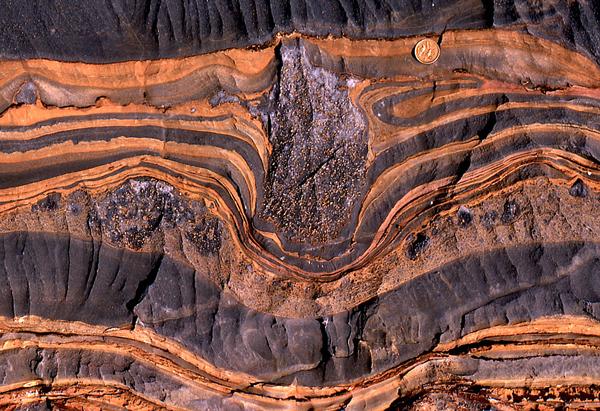 Пример за отломка вбита в по-долен седиментен слой под натиска на ледените шелфове от Намибия (монетата е сложена за мащаб)