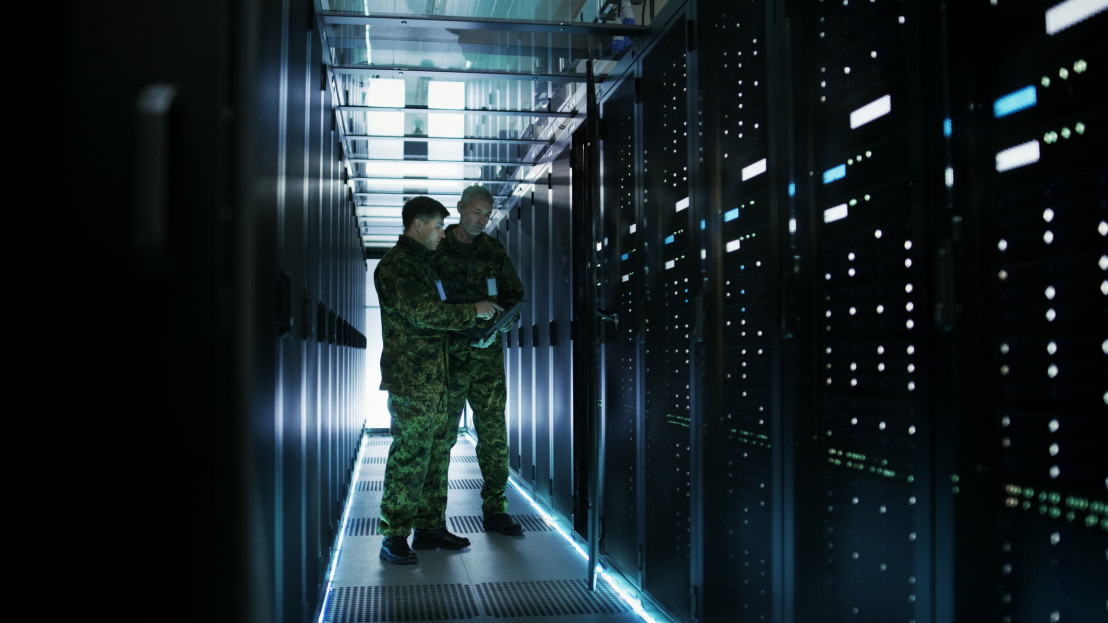 In Data Center Two Military Men Work with Open Server Rack Cabinet. One Holds Military Edition Laptop.