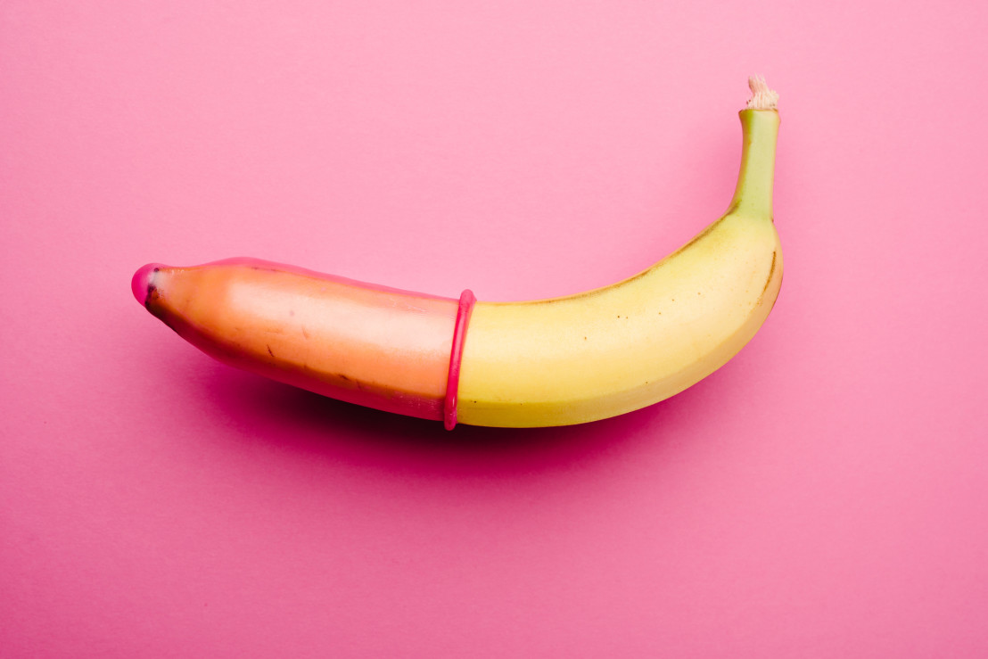 Pink condom on banana in front of pink background
