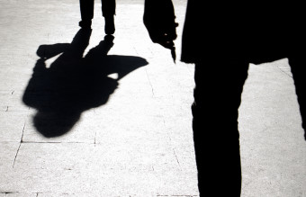 Blurry silhouette and shadow of a woman carrying a bag and a man holding sharp object following her