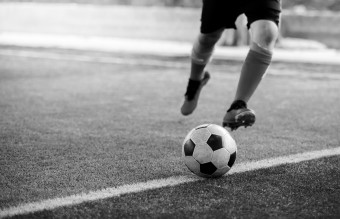 black and white image of the soccer player shoot ball on artificial turf.