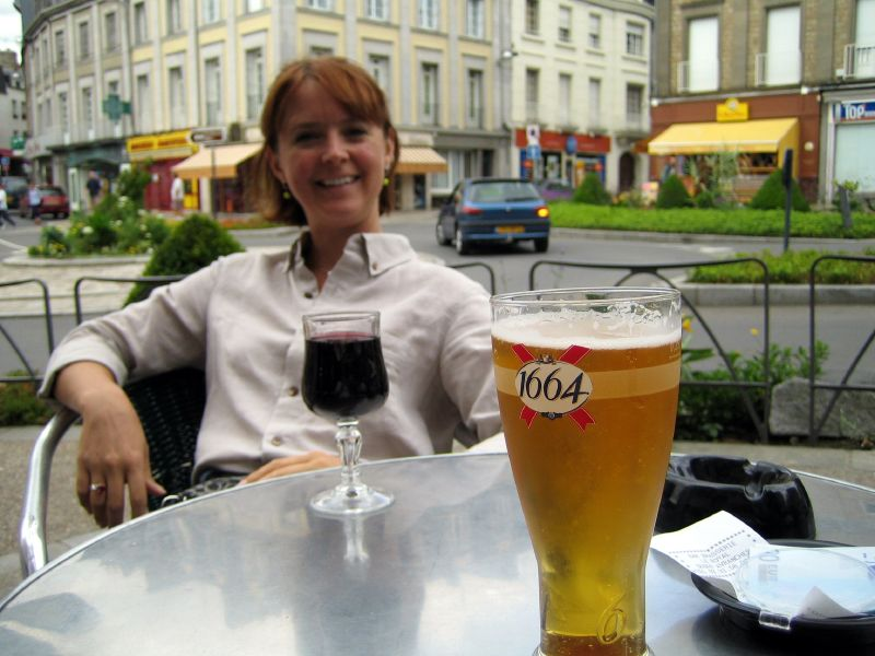 Lady_relaxing_next_to_glass_of_red_wine_and_glass_of_1664_beer