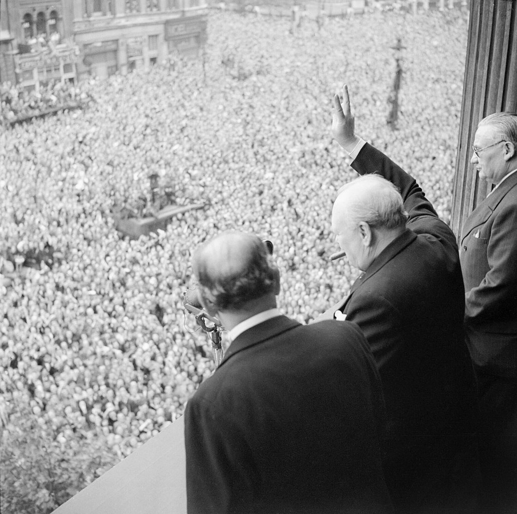 1030px-Winston_Churchill_waves_to_crowds_in_Whitehall_in_London_as_they_celebrate_VE_Day,_8_May_1945._H41849