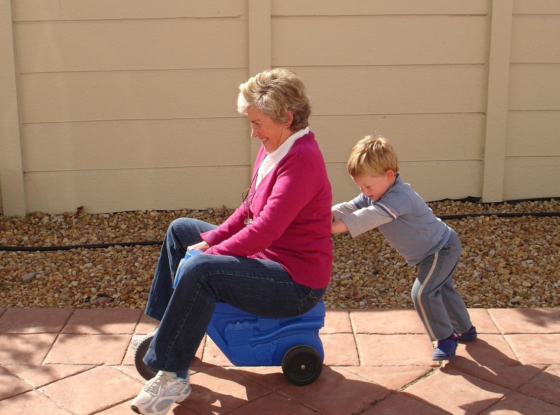 1280px-Child_pushing_grandmother_on_plastic_tricycle