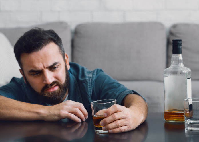 Ruined life with alcohol. Man sits at table and looks at glass in his hand