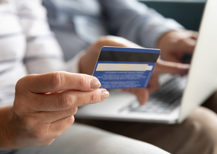 Female holding credit card making online payment, closeup view