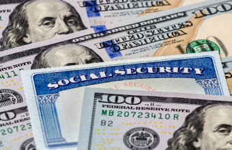 Social Security benefits identification card with 100 dollar bills