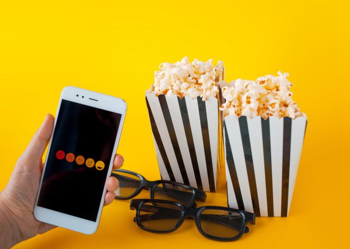 A hand is holding a smartphone in front of black-and-white paper boxes with popcorn and 3D glasses