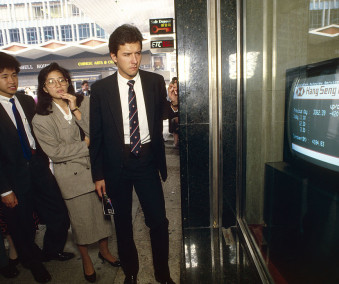 Black Monday. Business people watch a TV monitor in a bank