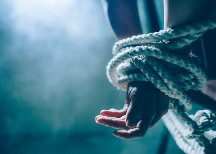 Close up and cut view of woman's hands died in a knot with a rope. One hand is up on another. Woman is tied behind her back. There is a window in dark room. Also there is a white smoke..
